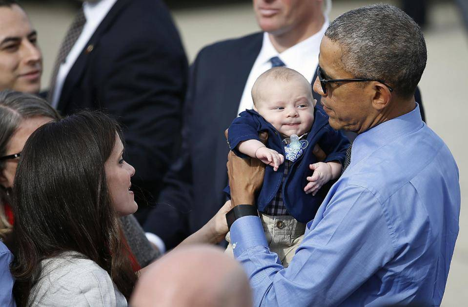 President Barack Obama holds 3 month-old Charlie Allsup as he meets with the crowd before departing on Air Force One at Moffett Federal Airfield Thursday, Feb. 11, 2016, in Mountain View, Calif. (AP Photo/Tony Avelar)